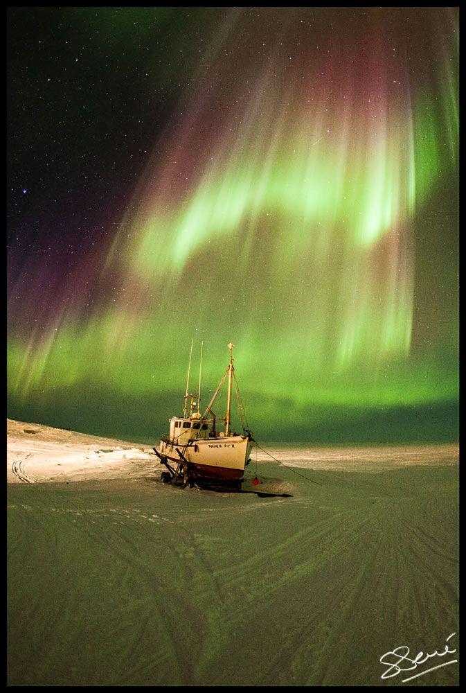 April 2013 aurora cascade and boat near Puvirnituq, Nunavik, Quebec, Canada.