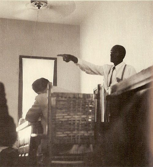 """Photograph taken at the trial of Emmett Till by the infamous civil rights photographer, Ernest Withers who also doubled as a FBI Informant. Withers defied the judge's orders prohibiting photography, documenting Till's uncle Mose Wright identifying J.W. Milam, which """"signified intimidation of Delta blacks was no longer as effective as the past,"""" and Wright """"crossed a line that no one could remember a black man ever crossing in Mississippi."""""""