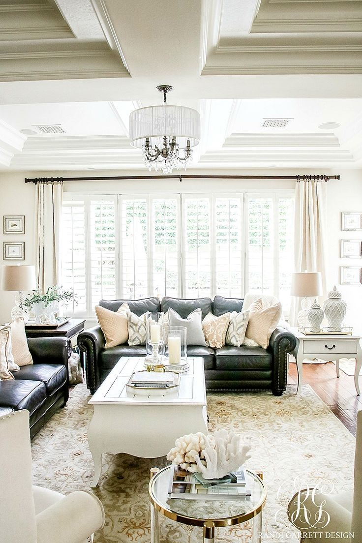 White family room with dark leather couches. Summery coral on lucite side table. Pretty chandelier and coffered ceilings. Soothing Summer Home Tour 2017 - Neutral Transitional Home Decor