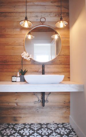 Edson Hill Home | Tania Kratt completely renovated the powder room, using a custom-built vanity made of Danby marble quarried in Vermont and reclaimed wood from an old barn. Its floor is covered with handmade white and black encaustic cement tile.