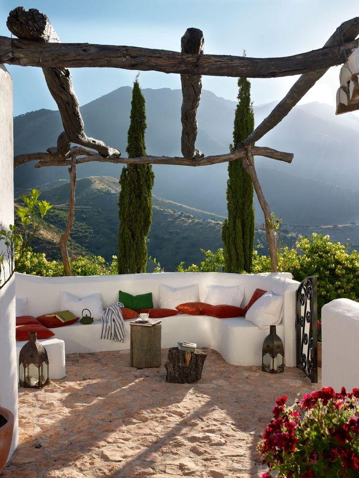 Con maravillosas vistas a la sierra, en este porche, con un amplio sofá de obra, es posible olvidarse de todo. Cojines rojos, deIkea, y farol, de La Galería. Las mesas auxiliares son dos troncos de árbol. El mueble