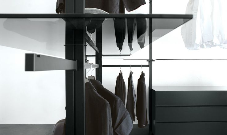 walk-in wardrobe in transparent black glass. The telescopic pole becomes the vertical support on which you can modulate shelves, shoe rack, rails for hanging, containers and drawers, in various materials and finishes.
