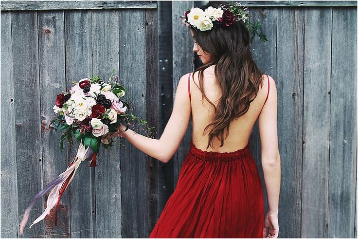 Low-backed crimson dress complemented by a luscious bouquet of cream, blush, and red roses,ruffled lisianthus,textural scabiosas, arching blooms, trailing details of sweet jasmine and rich foliages, all tied together with luxe plum and crimson ranunculus. Photo by: Light of Mine Photography.