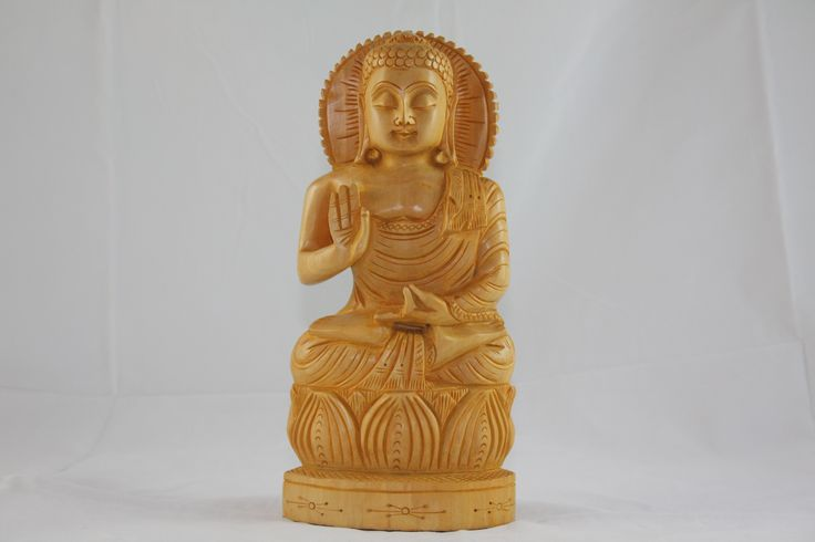 A beautifully carved light weighted wooden piece of enlightened Buddha meditating on a lotus flower.
