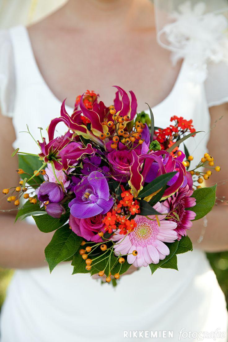 Kleurrijk bruidsboeket in de handen van de bruid. Met lichtroze en roze gerbera's, rozen, orchidee.  http://www.rikkemienfotografie.nl/