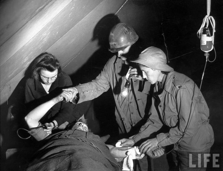 Medic working with two Army nurses administering blood plasma to patient critically wounded by shell fragments in tent of the US Army Medical Dept.'s evacuation hospital where 750 wounded patients are treated for wounds from the battlefields of Anzio (February 1944) ~