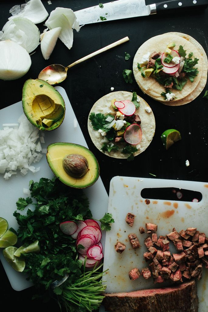 Flank Steak Tacos:  While the steak sears to form a thick, crisp crusty exterior I dice a pungent onion, sliver some radish on my mandolin and run a frilly bunch of cilantro under a running sink. As the steak rests I warm corn tortillas in the same pan as the steak cooked so they could soak up a bit of the meatiness still left in the warm pan.  Avocado makes a nice addition as would a garlic-laced cream sauce.