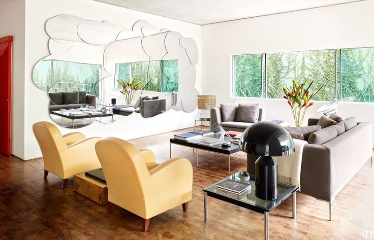 A cloud-shaped mirror by Estudio Campana reflects the living room and the garden; the firm also designed the bamboo-shade lamp and side table in the corner. An Antonio Citterio for B&B Italia sofa and matching daybed are grouped with a Maxalto cocktail table, also by Citterio; the armchairs are by Poltrona Frau, and the black lamp is by Oluce.