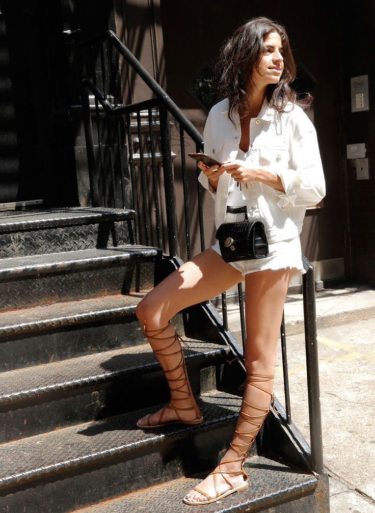 White cutoffs and jacket with a belt bag and gladiator sandals.