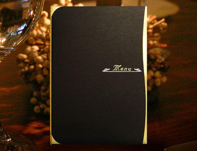 【プレサージュ(ブラック)メニュー表】とにかく高級感のあるプレサージュ(ブラック)のメニュー表。ベースの黒紙は紙質がしっかりしていて少しマットな感じがより一層、高級感の漂うものになっています。その紙と合わせてゴールドで光り輝く紙はポイントで使われています。夕方からの結婚式、披露宴などで人気の高いペーパーアイテムです。