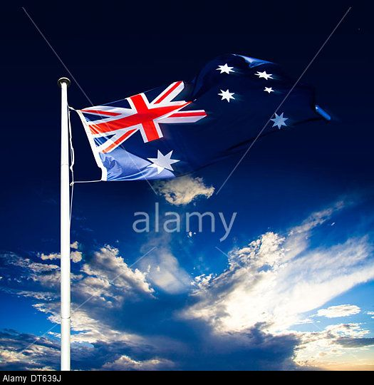 Australian Flag Blowing In The Wind On A Flagstaff With A Beautiful Cloud Sunset In A Breeze Of Patriotism