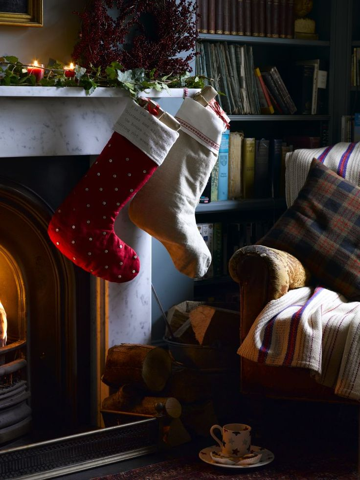 Decorate the mantlepiece with candles, green foliage and red berries to create a warming look and hang stockings ready to be filled on Christmas Eve. housebeautiful.co.uk