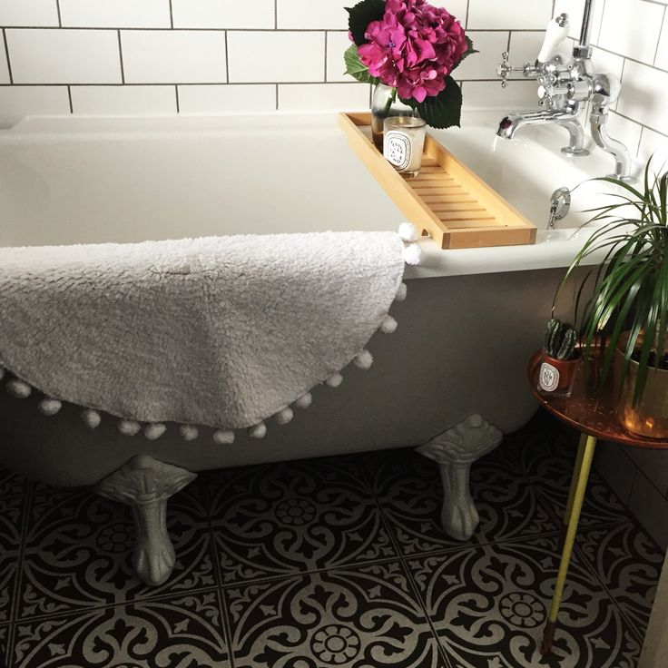 My small but beautiful bathroom at home, gorgeous patterned tiles, roll top corner bath, clean white tiles to make the space appear bigger finished off with a beautiful white Pom Pom bath mat and flowers!