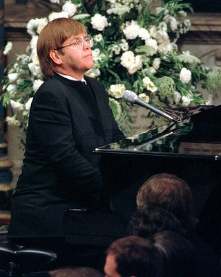 Elton John  plays a specially re-written version of his classic Candle in the Wind during the funeral service for Princess Diana in 1997.