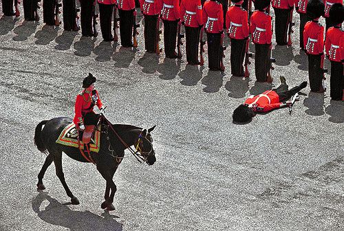 Horse Guards Parade, 1970, Queen Elizabeth riding her horse Burmese during the Trooping of the Colour ceremony. A Grenadier Guard lies prostrate at attention as all good Guardsmen should when they faint!