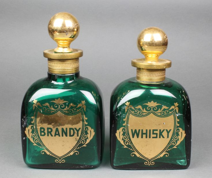 """Lot 7, A Continental green glass flattened whisky decanter and stopper with gilt decoration 8"""", a ditto brandy decanter and stopper 9 1/2"""", est £50-75"""