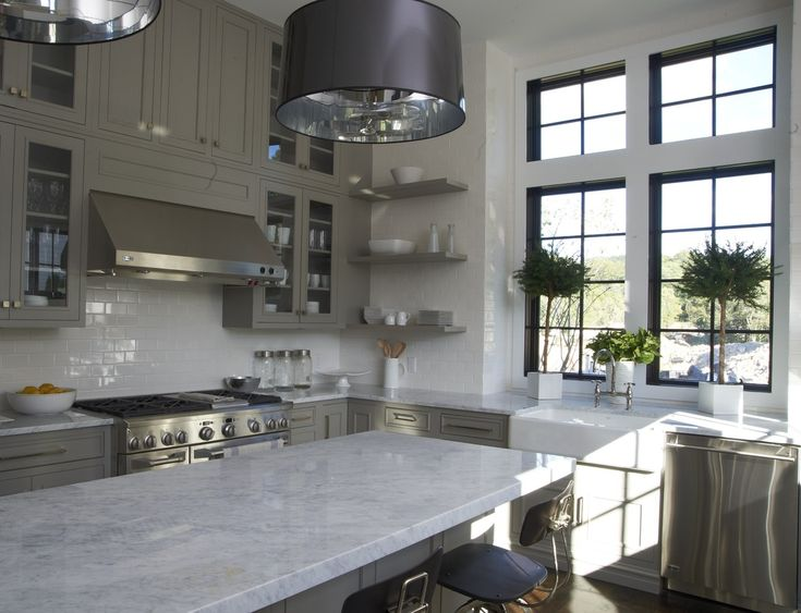 Gray cabinetry, marble counters and island, white subway tiles, farm sink, stainless