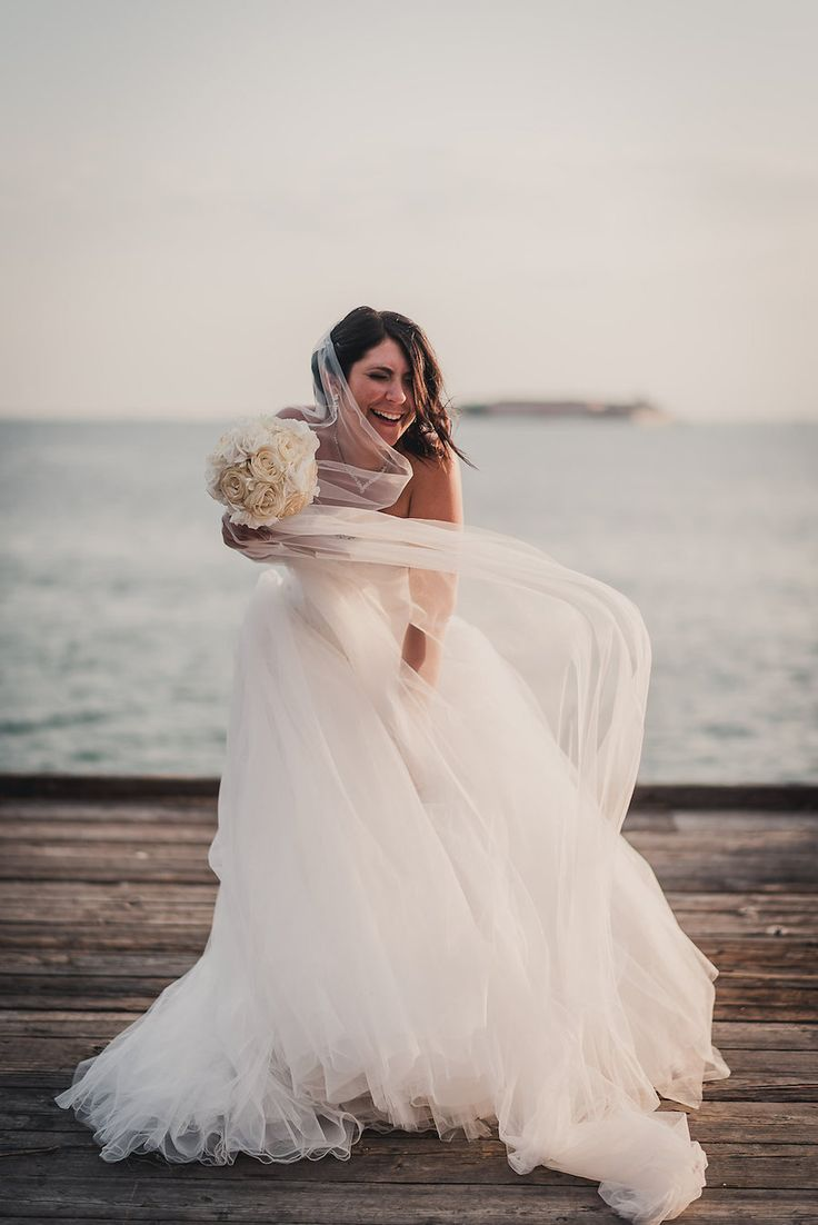 Beautiful beach wedding with large flowy tulle wedding dress and veil blowing in the wind.