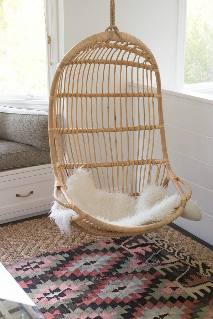 The hanging wicker chair brings a charming outdoor-like element to the indoor design. A fur seat cushion throw adds a soft texture to the chair and compliments the white base of the room. A southwestern patterned rug adds a layer of color over the thick weaved rug below.