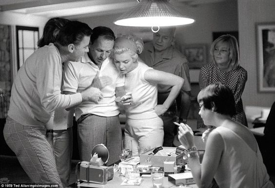 Frank Sinatra and Marilyn Monroe (centr) cuddle up while having drinks with Peter Lawford and his wife Patricia Kennedy as well as Swedish star Mai Britt (right)