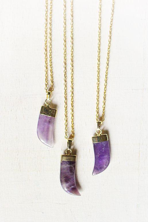 Guldpläterat halsband med en hornformad berlock av lila ametist. | Gold plated necklace with ametist tusk pendant.