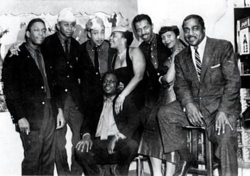 John Coltrane (feeling good), Paul Chambers, Red Garland, Miles Davis (sitting), unknown female , Philly Joe Jones, unknown female and Jimmy Witherspoon at a Christmas party.
