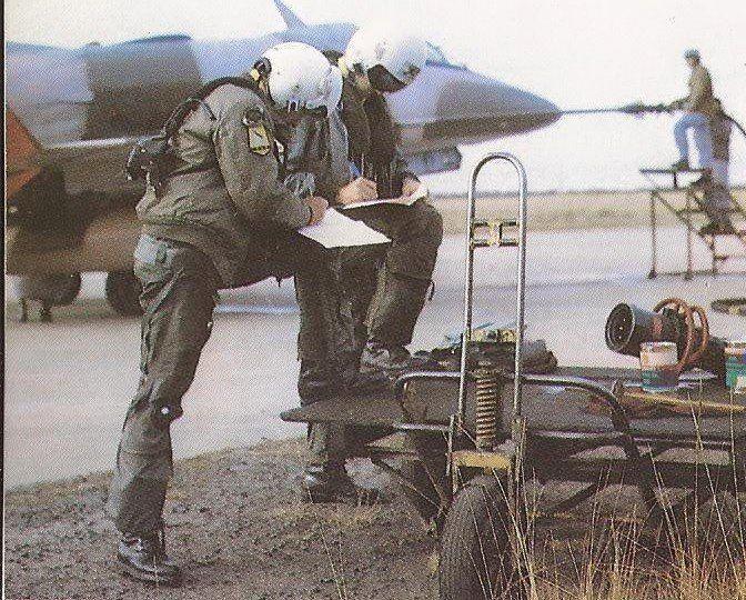 """Avión A-4 C """"Skyhawk"""" realizando un reaprovicionamiento de combustible """"en caliente"""" (con el motor encendido) y dos pilotos con sus cascos puestos debido al ruido del motor. En la V Brigada Aérea. Foto del 85' - 86'"""