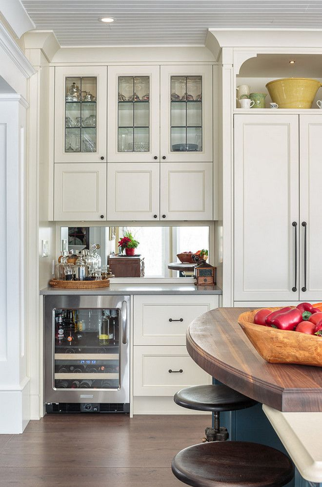 The kitchen bar comes with a beverage refrigerator. Mirrors were used as backsplash to reflect light and the river view. Farmhouse Kitchen with Blue Island