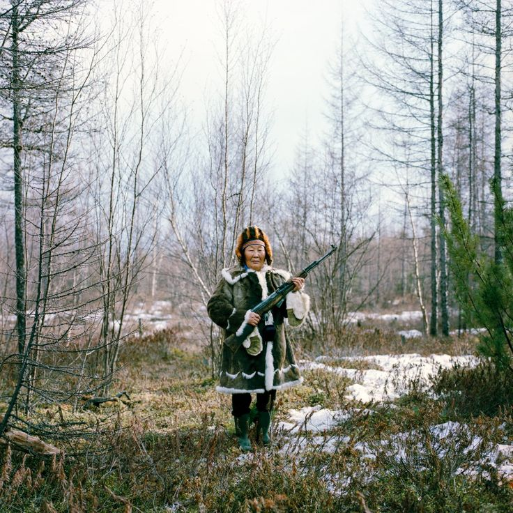 Maria Ivanova, seen here in traditional Evenk dress, is holding a rifle used for practice shooting in the forest after a family picnic in Zhigansk. The Evenk people are an indigenous ethnic group from Northern Asia. The Russian Evenks live mostly in the Siberian taiga, where their population is around 35,000.