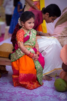 South Indian Kid - Small Kind in a Orange and Pink Saree with Green Pallu and a Golden Waistbelt | WedMeGood #wedmegood #indianbride #indianwedding #southindianbride #southindiankid #saree #waistbelt