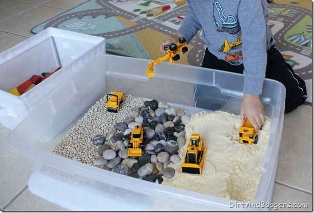 White beans. River rock, Cornmeal.   Construction trucks. I placed everything into a plastic box.  I also added a few blocks so J could build something if he wanted to.    J's favorite part was using his diggers to fill up the dump truck.  This was a great sensory experience for J because of all the different textures and smells inside the box.