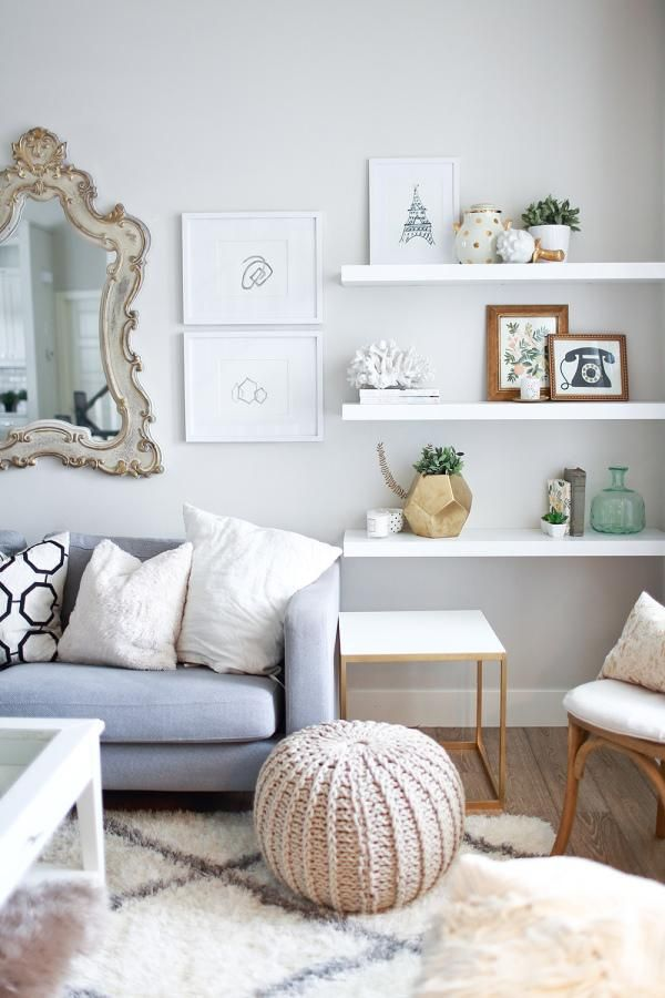 Love his neutral gray and cream living room accented with a mix of modern objects, cozy floor pouf and throw pillows, and a baroque mirror over the couch.