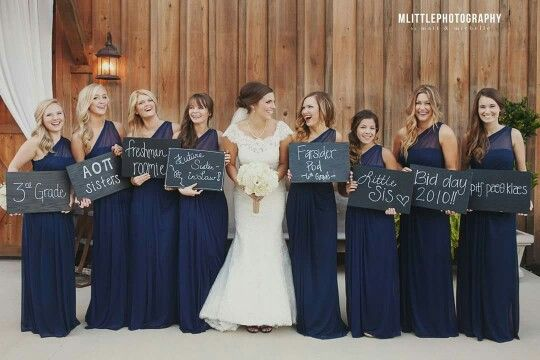 Cute idea. Bridesmaid's holding signs of how they met the bride