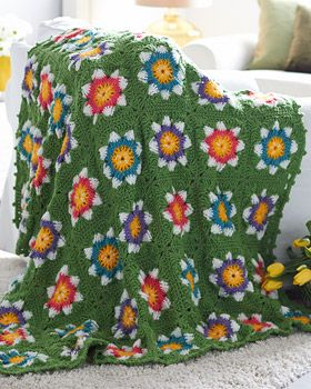 Set on a deep green background, these flowers in four different colorways truly pop! Shown in Bernat Super Value. #crochet