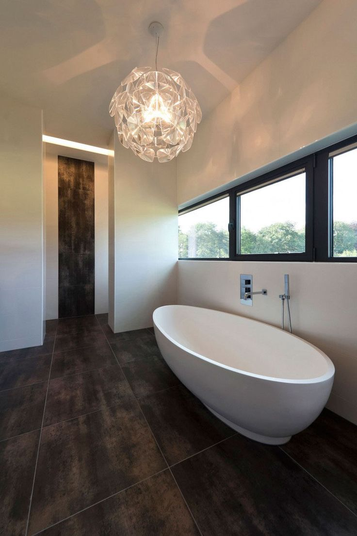 Bathroom Tile Ideas - Use Large Tiles On The Floor And Walls // The large dark tiles in this bathroom allow this bathroom to feel extra lavish, and the continuation of the tile up part of the wall just outside the bathroom makes the space feel connected to the rest of the house.