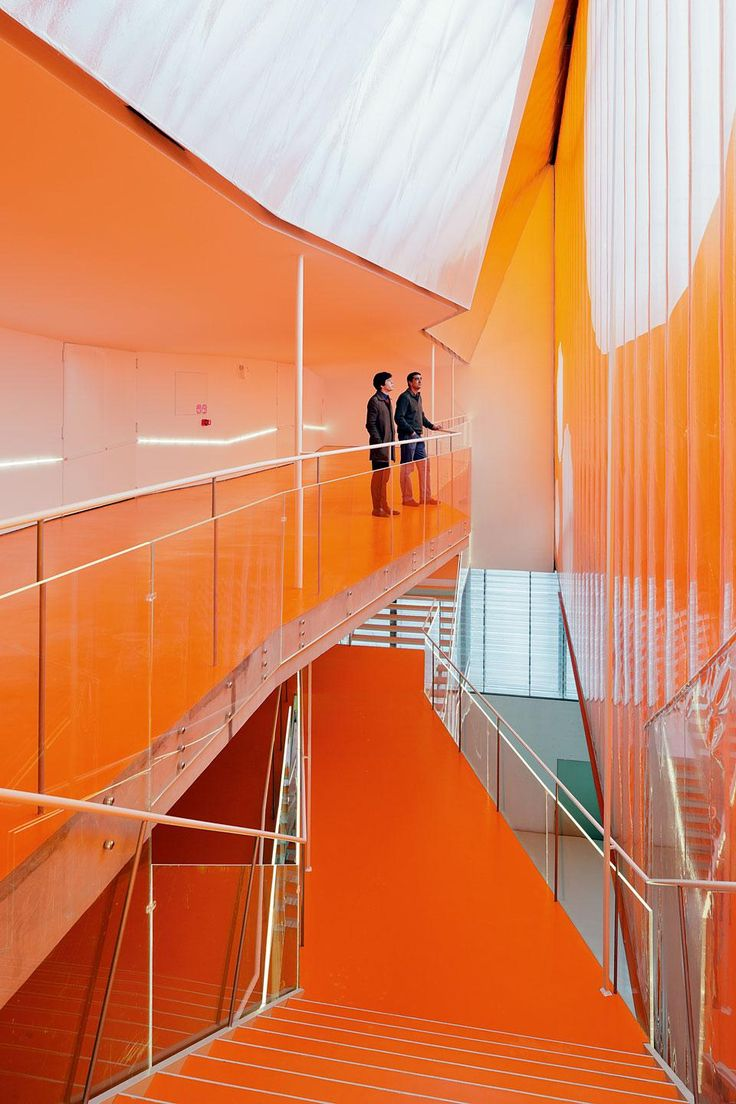 by selgascano: The upper levels are drenched  in a permanent sunset thanks to two 15x60-metre orange coloured  ETFE sheets anchored to a steel frame that create a soft,  billowing intermediate facade.