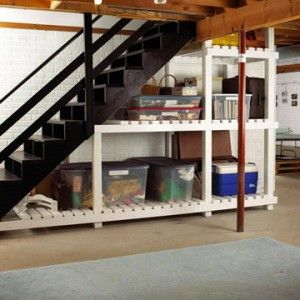 Storage solution for one unfinished basement. Notice black stairs. White storage exteriors, rug.