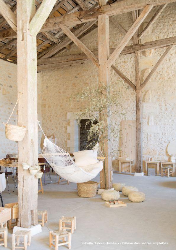 Grange: sol minéral dalle béton, charpente bois brut et sous face de toit visible. Pierres jointoyées.