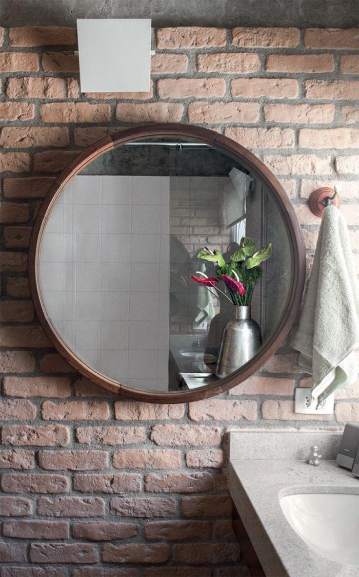O espelho redondo (5 Décadas) teve que ser posicionado na parede lateral, coberta com um acabamento cimentício que imita tijolos aparentes (Passeio Revestimentos).