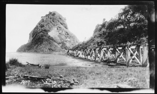 View of tramway trestle alongside the lagoon at Piha. Lion Rock in background.