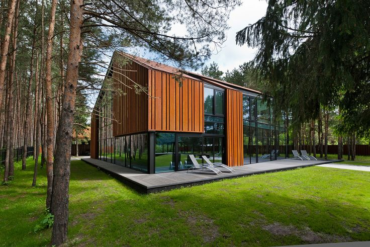 """This home located in the middle of the woods in Kaunas, Lithuania was constructed in 2011 by Studija Archispektras. The outside of the structure is a pleasant mixture of wood and glass, the latter of which reflects the woods which surround the home. The inside is spacious, bright, and stylishly modern. A House in the Woods of Kaunas by Studija Archispektras: """"The house is situated on the river shore. The.."""