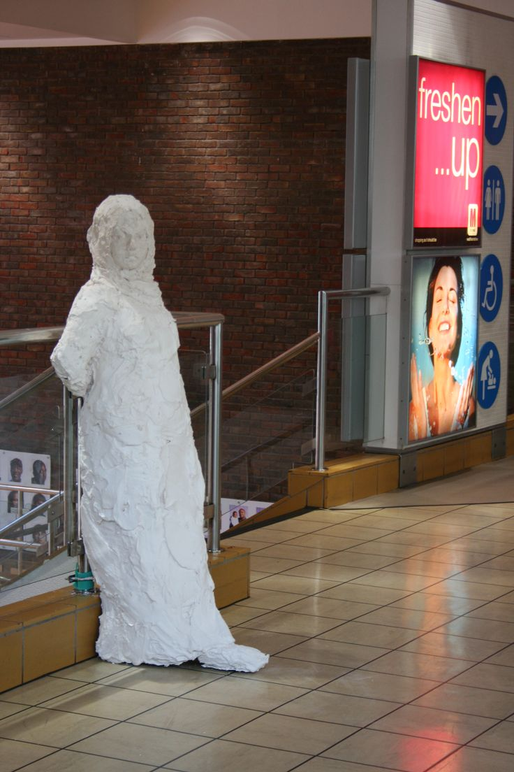 Waiting: life-size plaster sculpture in a shopping mall