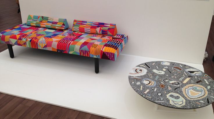 Multicoloured sofa and stone side table.