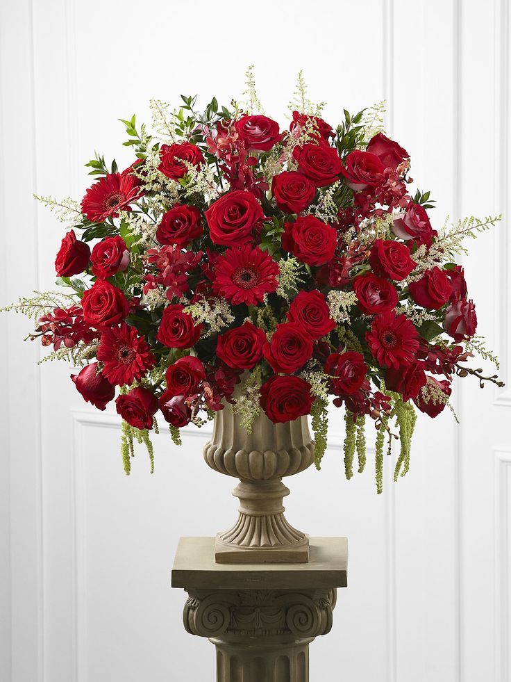 This spectacular altar arrangement blooms with the magic of the love's finest moment. Red roses, white astilbe, bi-colored red and white roses, red mokara orchids, red gerbera daisies and fresh myrtle are brought together in a resin urn