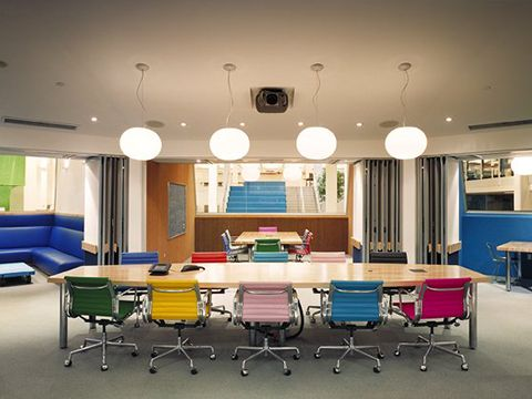 Eames Aluminum Group Chairs bring bold pops of color to this conference room. Photo by: Jensen Architects