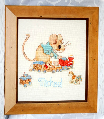 A beautiful framed cross-stitch embroidery depicting a cute little boy mouse playing with his train. Sitting in the train are his two favourite teddies. This charming picture will look aborable on the wall of a little boy's room. Personalise with the child's name. Ideal birthday gift or for a special occasion.