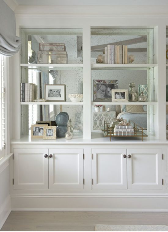 Mirrors at the back of a bookshelf. Love it - space saving and makes the room look massive.