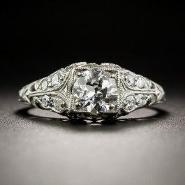 This darling  vintage engagement ring, is crafted in platinum circa 1920s-30s, by the notable jewelry manufacturer of yesteryear - Traub/Orange Blossom. A bright white and beautiful European-cut diamond, weighing .60 carat, sparkles between double pairs of small glittering diamonds, followed by stylized orange blossoms embossed into the top of the ring shank. We seldom use the clarity grade SI3, however, this one meets the criteria with eye-clean transparent inclusions.Currently ring size 5.