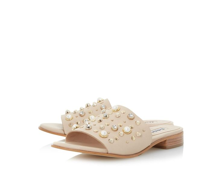 Elevate your casual summer wardrobe with the stunning Linz mule sandal. Showcasing a classic silhouette with a wide front strap and flat heel. The pearl, stud and jewel embellishment completes this slip on style.