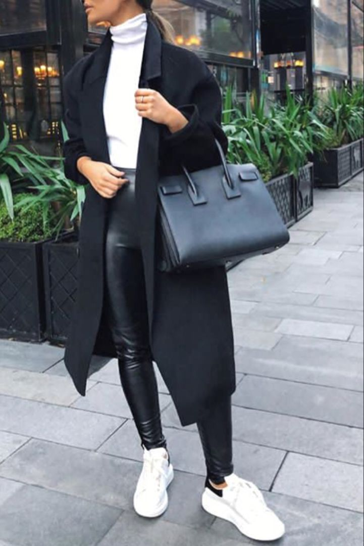 fashion woman fall winter with a long black coat white sneakers a sweater